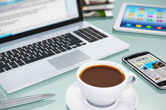 Modern office workplace. Modern office business workplace with laptop PC, touchscreen smartphone, tablet computer and white porcelain cup of black coffee Stock Photo