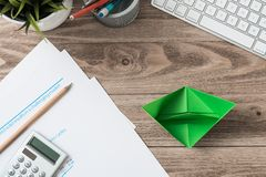 Modern office workspace with green paper ship. Eco-friendly business idea. Flat lay wooden desk with computer keyboard, calculator and documents. Creative royalty free stock photos