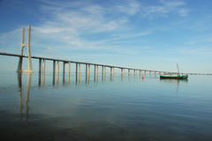 Modern and old. Traditional Tejo boat with Vasco da Gama bridge on the back Stock Photos