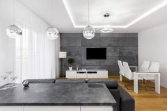 Apartment with concrete wall tiles. Modern, open plan apartment with concrete wall, lamps, tv, table and chairs royalty free stock photo