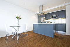 Modern open plan living area. With dining table and fully fitted kitchen Royalty Free Stock Image