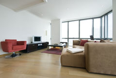 Modern open plan living room. With contemporary furniture and floor to ceiling windows Stock Photos