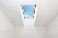 A modern open skylight mansard window in an attic room against blue sky. Stock Photography