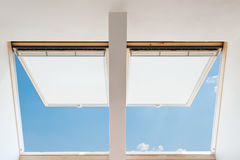 A modern open skylights mansard windows in an attic room against blue sky. Royalty Free Stock Photo