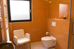 Modern Orange Bathroom. Modern bathroom with orange tiles, white appliances and a white chair Stock Photography
