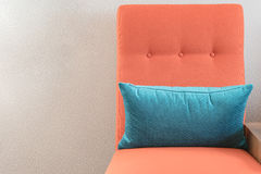 Modern orange chair with blue pillow Royalty Free Stock Images
