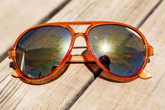 Modern orange sun glasses with mirror glasses isolated on a wooden background Stock Photo