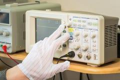 Modern oscilloscope, man`s hand adjusting wave signals, closeup Royalty Free Stock Photo