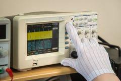 Modern oscilloscope, man`s hand adjusting wave signals, closeup.  royalty free stock photography