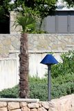 Modern outdoor light resembling bedroom style lamps next to small young palm tree surrounded with traditional stone wall and other royalty free stock images