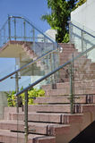 Modern outdoor stairway with glass wall panels. Leading from the garden to the pool floor, a stairway with glass wall panels in the railings Stock Photos