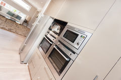Modern oven and refrigerator fixed to the wall with pantry cupbo Royalty Free Stock Photo