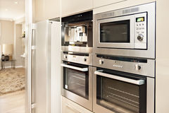 Modern oven and refrigerator fixed to the wall with pantry. Luxurious kitchenware including silver oven and refrigerator in the kitchen which has a wooden floor Royalty Free Stock Photography