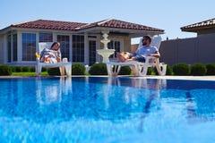 Modern paar die tan krijgen onder de zon dichtbij pool stock foto