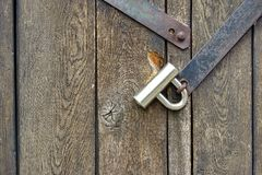 Modern padlock on textured black wooden door Royalty Free Stock Photos