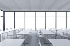 A modern panoramic classroom with white copy space in the windows. White tables and white chairs. 3D rendering Stock Images
