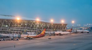 15 July, 2018. Pudong Airport, Shanghai, China. Modern passenger airplanes parked to terminal building gate at stock photos