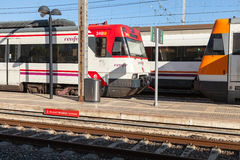 Modern passenger electric trains stand on railway station Stock Photos