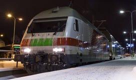 Modern passenger train on the railway station at night Royalty Free Stock Photo
