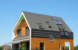 Modern Passive House Exterior. Modern energy efficiency house with skylight windows and solar panels on the roof top royalty free stock images
