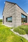 Modern pebble stone wall house. With large windows, surrounded by wild grass Royalty Free Stock Photography