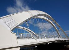 Modern Pedestrian Bridge with Double Arches. A new arch bridge with cable suspension and a deep blue sky Stock Photos