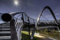 Modern footbridge. Modern pedestrian footbridge with decorative arch over a river Royalty Free Stock Image