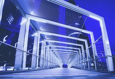 Modern pedestrian overpass. This bridge links pedestrians and commuters to the main financial Central business district of major City. It's blue and modern Royalty Free Stock Photos