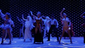 Modern performance with unusual heroes, dances and songs in theatre. People with a greasepaint and wearing scenic costumes are singing and dancing in the modern stock footage