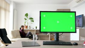 Modern personal computer with big green screen chroma mock up. In the living room of comfy house. A man walks in background while the TV is on and sits on the stock video footage
