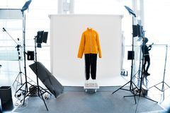 Modern Photo studio booth with LED lighting. Modern Photo studio booth with LED professional lighting equipment around Yellow Orange Clothes dress on Mannequin royalty free stock images