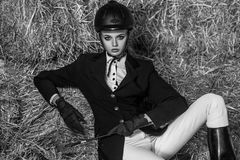 Modern picture. Young adult woman in equipment sitting on hay royalty free stock photos
