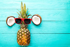 Modern pineapple with sunglasses and coconut  on blue wooden background. Top view Royalty Free Stock Photography