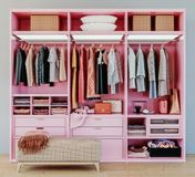 Modern pink wardrobe with clothes hanging on rail in walk in closet design interior. 3d rendering royalty free stock photo