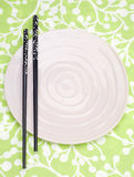 Modern Place Setting. With Pink Plate, Black Chopsticks on Green Patterned Background stock photography