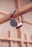 Modern plastic headphones with cable hanging Royalty Free Stock Photos