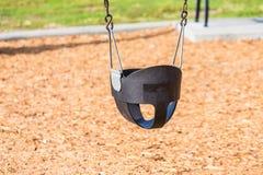 Modern Plastic Swing Over Wood Chips Stock Image