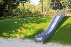 Modern playground with a metal slide inscribed in the landscape design with a ladder of plastic shells made on the hillside. Park, color, red, happy royalty free stock photography