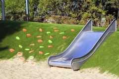 Modern playground with a metal slide inscribed in the landscape design with a ladder of plastic shells made on the hillside. Park, color, red, happy royalty free stock photos