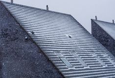 Modern pointy rooftop covered in snow during winter season, snowy cold weather, dutch architecture. A Modern pointy rooftop covered in snow during winter season stock photos