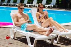 Modern pojkvän och flickvän som använder deras solbada för telefoner Royaltyfria Bilder