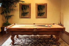 Modern pool game table. A beautiful pool game table takes center stage in the pool entertainment room of this modern home royalty free stock images