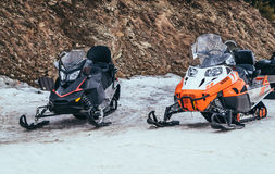 Modern powerful snowmobiles. Speed winter transport in the mountains. Pair of modern powerful snowmobiles on the background of rocks. Active trip in the Royalty Free Stock Photos