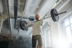 Modern Powerlifter Lifting Barbell in Gym. Portrait of modern strongman weightlifting with heavy barbell performing shoulder press during workout in sunlit gym royalty free stock photography
