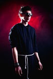 Modern priest. Wearing sunglasses standing over dramatic red background Royalty Free Stock Images