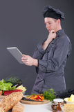 Modern professional chef uses the tablet for a selection of dish Royalty Free Stock Photography