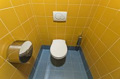 Modern public toilet. Modern and stylish public toilet with tiles in mustard and light blue color Stock Photography