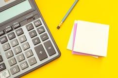 Modern räknemaskin och blyertspenna med klistermärkear för anmärkningar på en gul bakgrund, bästa sikt fotografering för bildbyråer