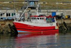 Modern röd fiskebåt tillsammans med hamnplatsen Royaltyfria Bilder