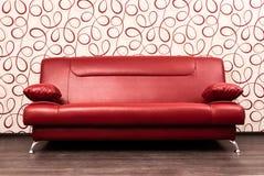 Modern röd sofa framme av väggen Royaltyfria Bilder